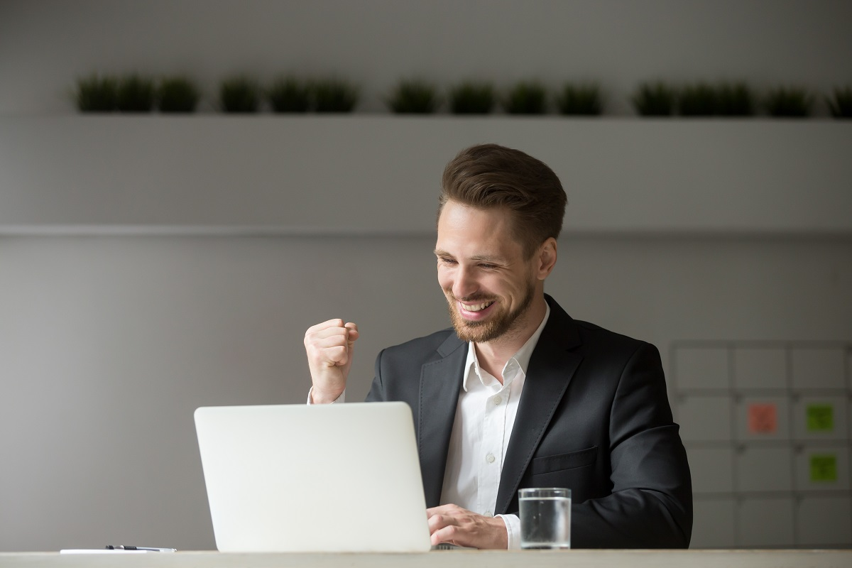 man wearing business attire infront of computer